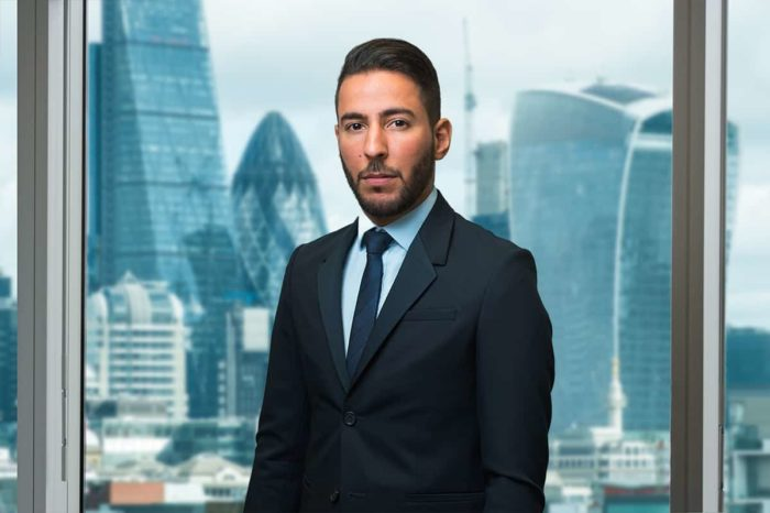 Company website profile photograph of man in London office with City view.