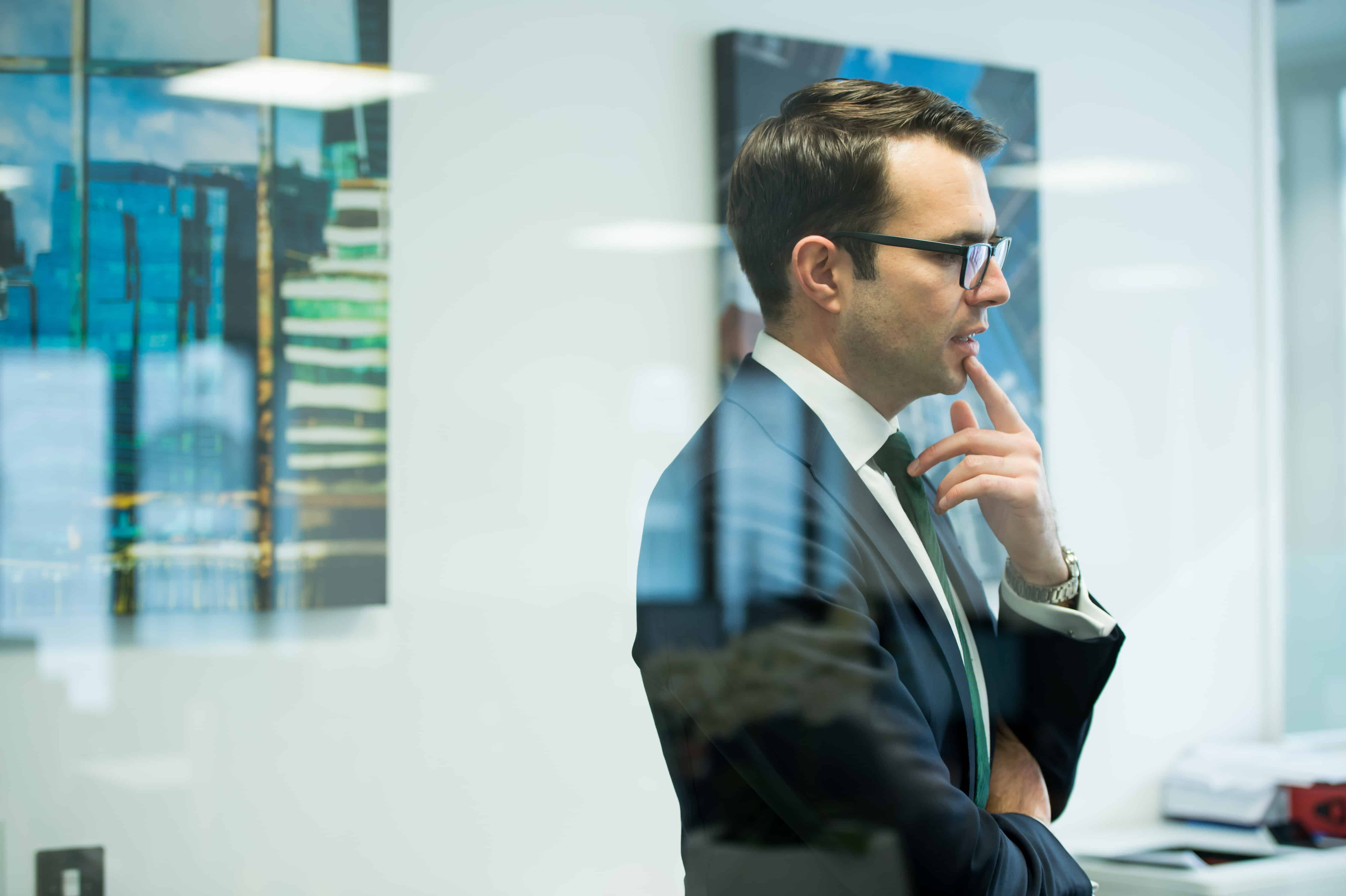 Businessman thinking in corporate offices in London