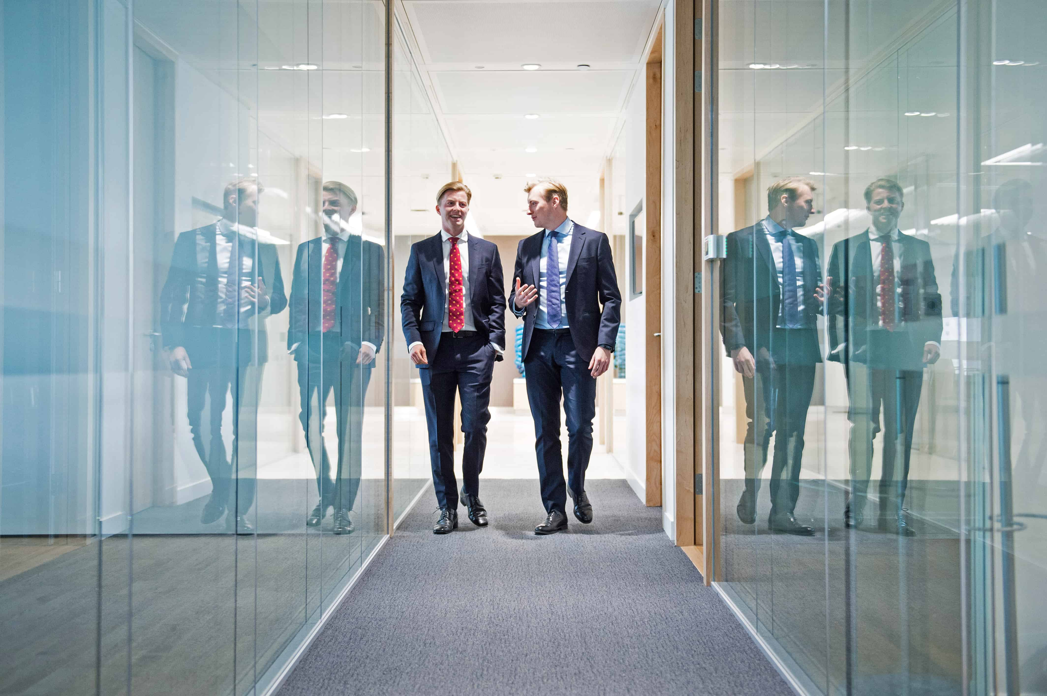 Two businessman walking and talking in corporate offices London