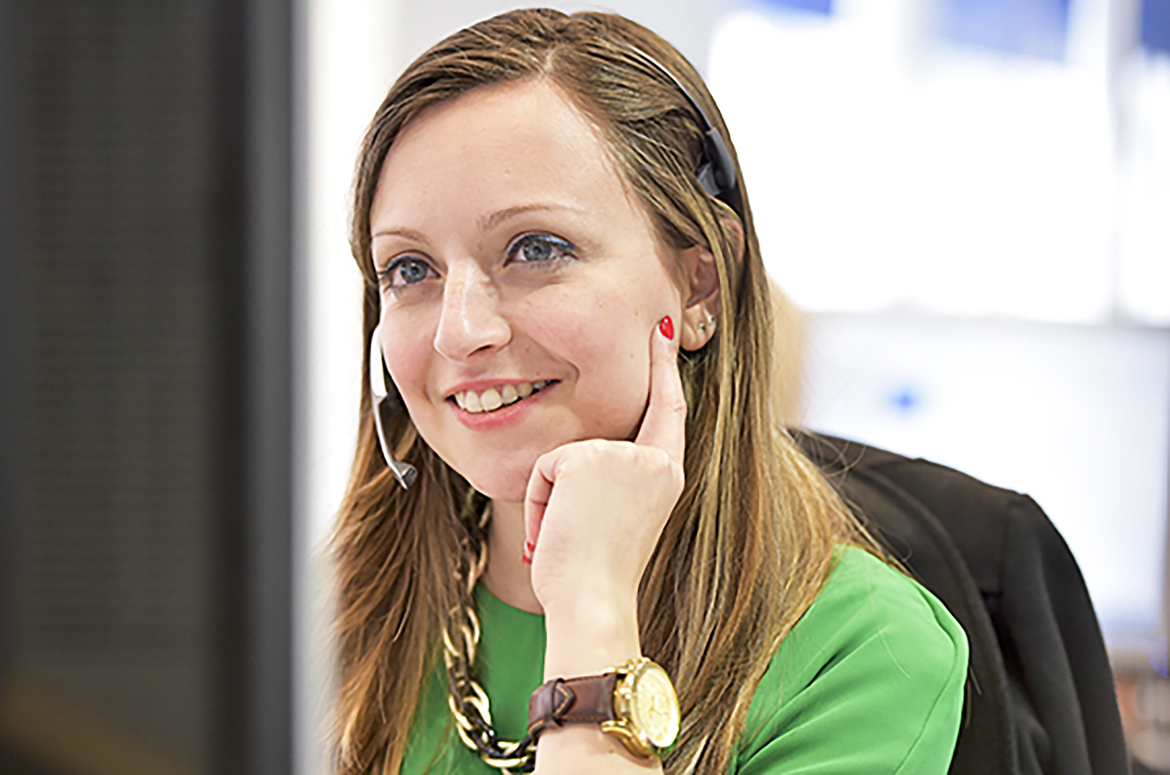 Smiling business woman with headset in London offices.